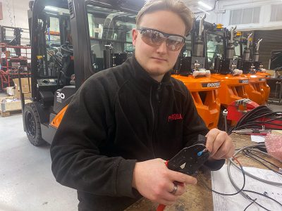 Apprentice supporting the truck conversion production line
